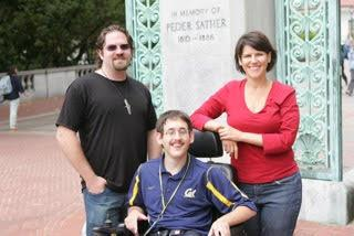 a student in a wheelchair with two people standing next to him in front of Sather Gate