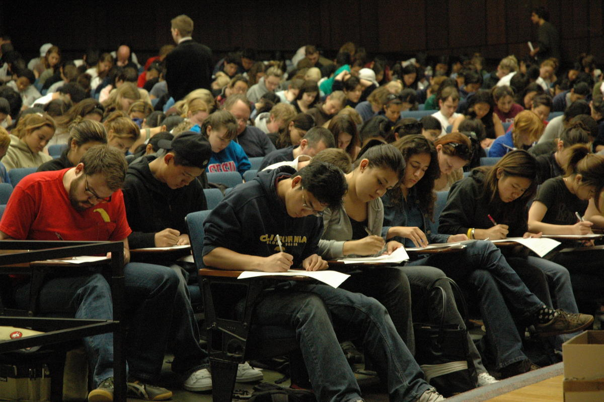 Large classroom of students taking an exam.