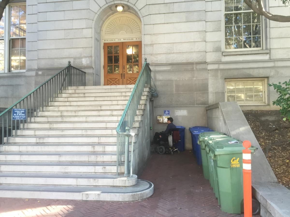 Basement entrance to Wheeler Hall on the north side of the building. A student in a wheelchair is seen turning left under the staircase that leads to the basement entrance's doors.